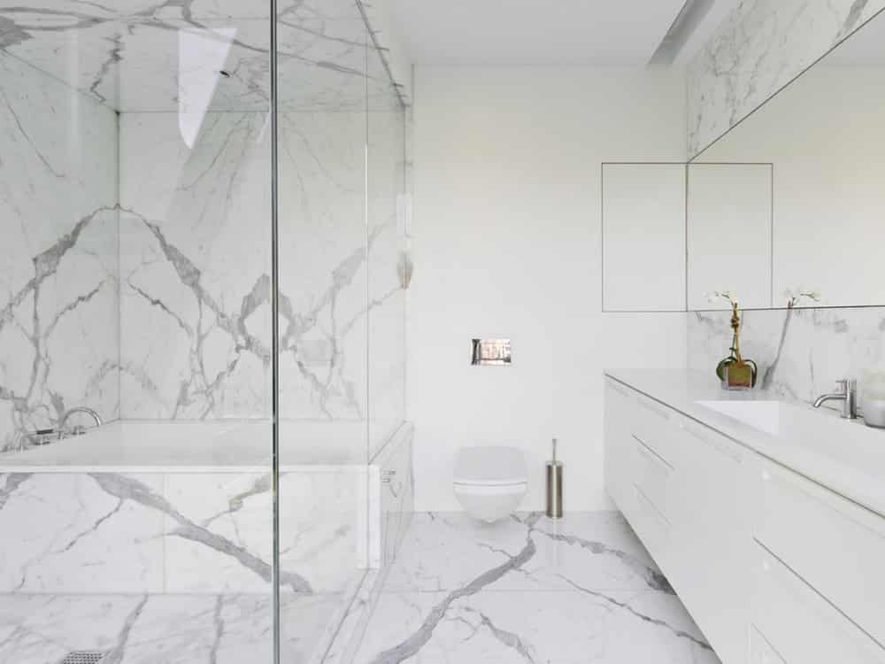 remodeled bathroom featuring marble floors, walls, and countertops with a white vanity and large glass shower with a tub in it