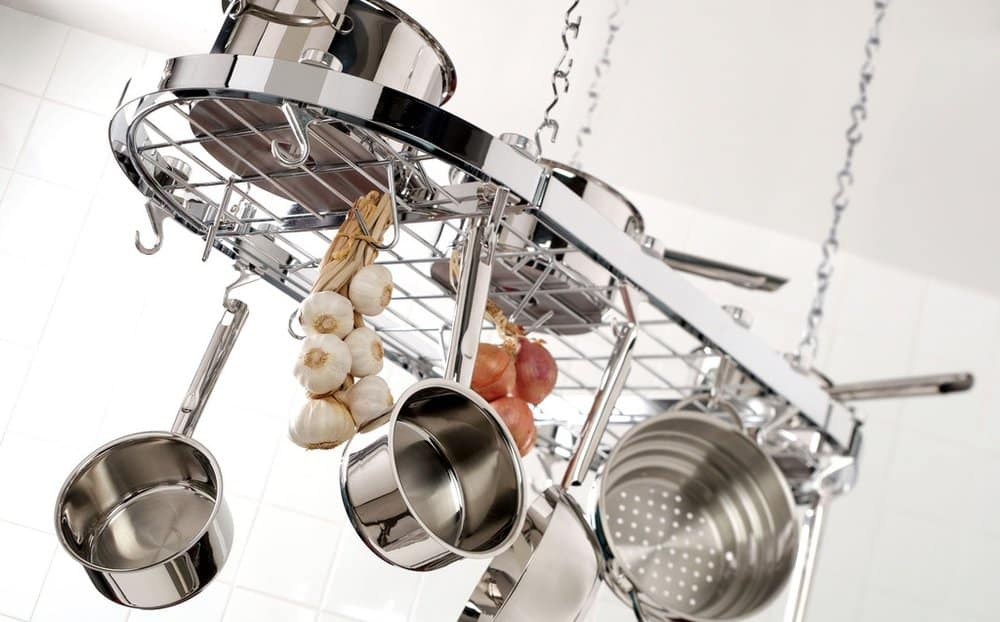 stainless steel potrack with pots, pans, garlic, and onions hanging from it