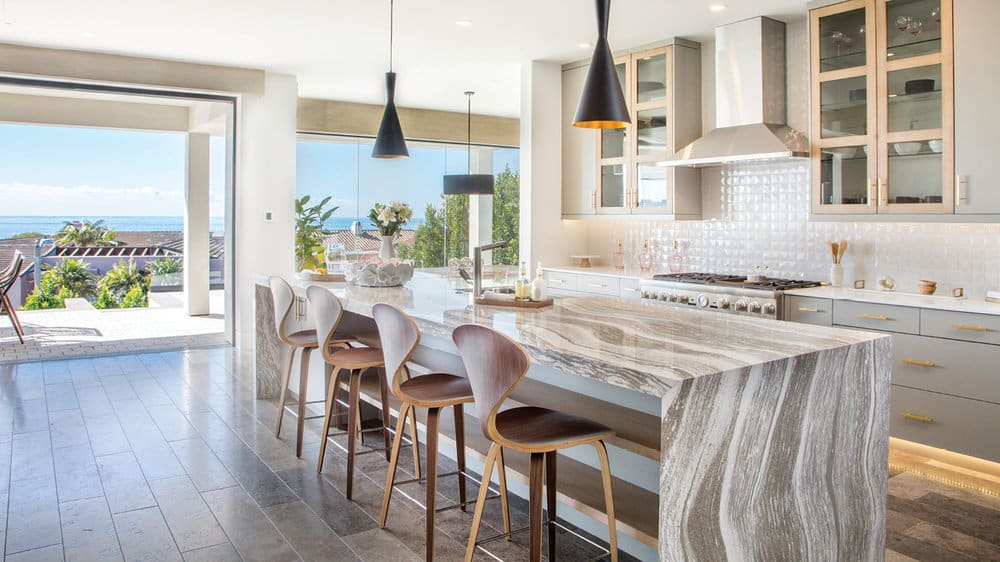 bright coastal kitchen with quartz countertops open to patio