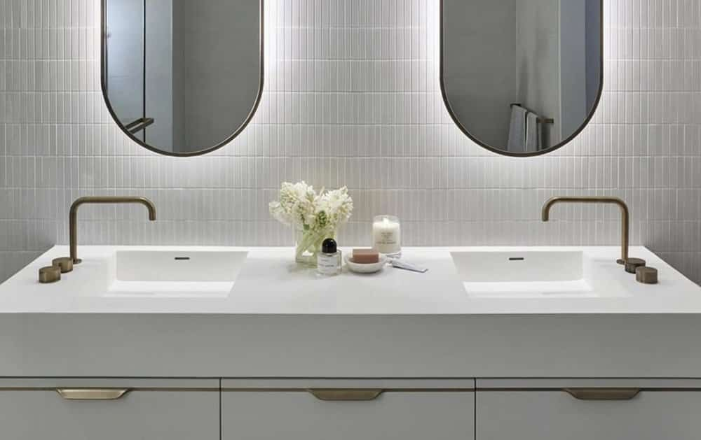 remodeled bathroom with white wall tile, white vanity and countertop, backlit mirrors, and two sinks with side-mounted faucets