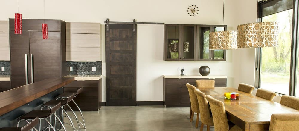 remodeled kitchen with two-toned cabinetry, wood tones throughout, and a dark wood sliding barn door