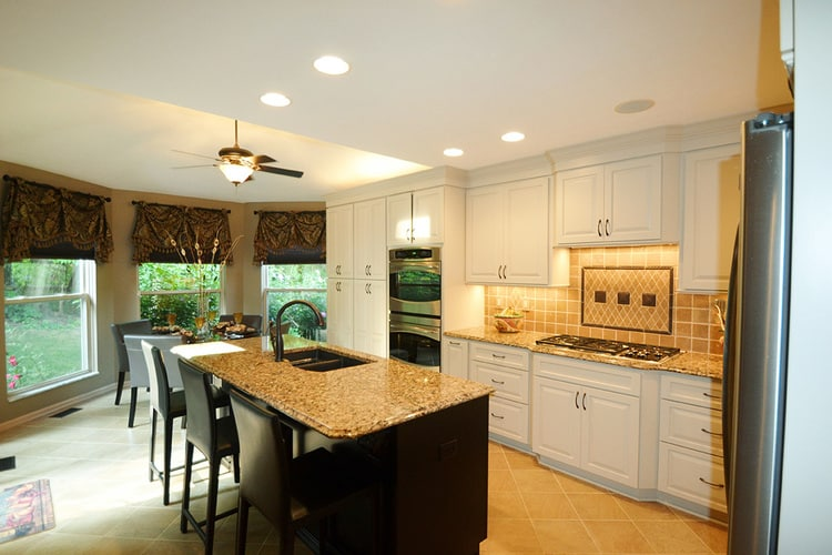 kitchen remodel with white cabinets, earth tone tile floors and backsplash, with granite countertops
