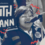 "A young Judy Heumann speaks at a microphone outside. She wears octagonal glasses and a button on her jacket that reads ""sign 504."" There is a mix of typed and drawn text on top of the image that reads ""1970's Disability Revolution, Judith Heumann,"" on the left and ""Oct 28-29"" and the KU signature on the right."