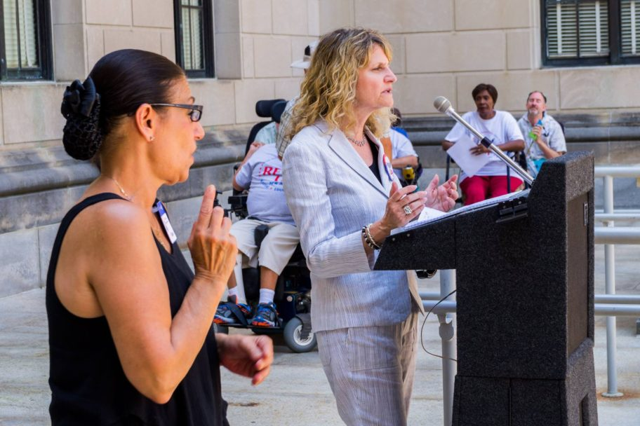 female in business suit standing at podium outside with a sign language translator beside her speaking to a group of people outside