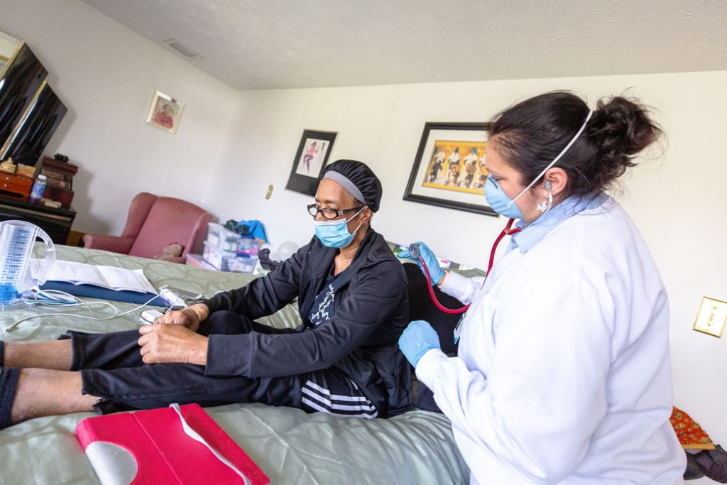 consumer in a home setting receiving home health care wearing masks, gloves and other protective gear during the COVID pandemic