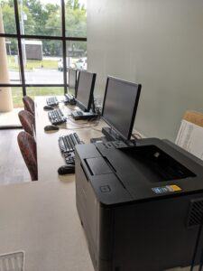 3 desktop computers and a printer sitting on a conference style table in a lobby