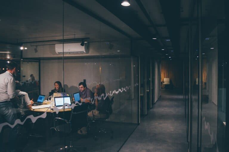 People huddled in boardroom at night