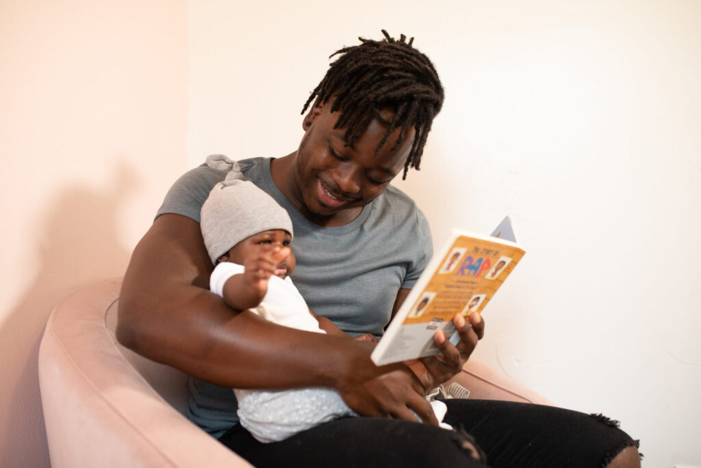 parent reads to newborn