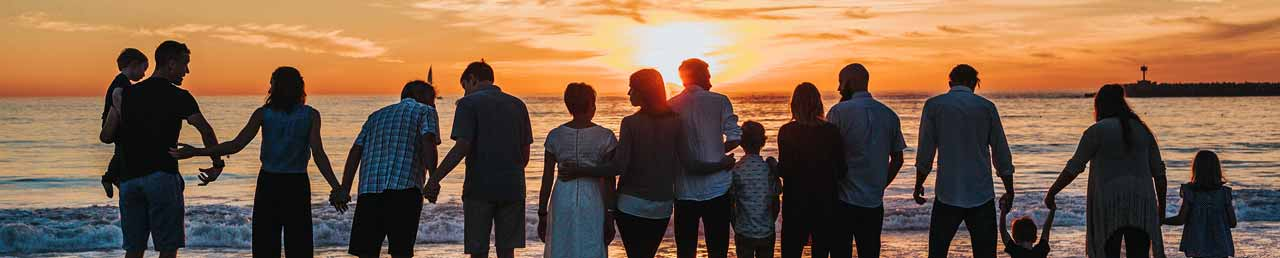 Families watching a sunset from the beach.