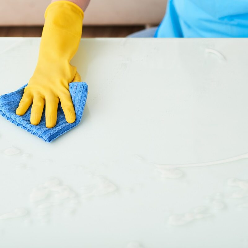 Gloved hand on woman cleaning white surface of table