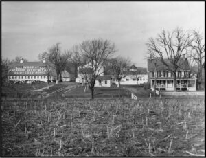 Historic black and white photograph of the farm property showing the barn, farmhouse, and other support structures.