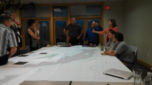Members of the design team and conservancy discuss the design of the project around a large meeting table. A large printed site plan covers most of the table.