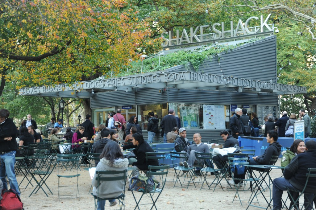 Photograph of Shake Shack. The tables and chairs in front of the structure are almost full with people.