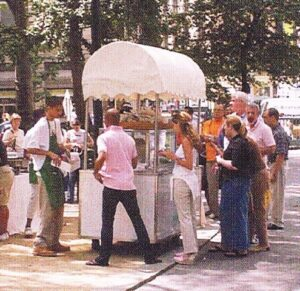 Older, grainy photograph showing people lining up at the park's hot dog cart.