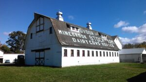 """Photograph of the Dvoor barn. On the roof is painted """"Dvoor Minebrook Stock-Farm Dairy Cows - Horses"""""""