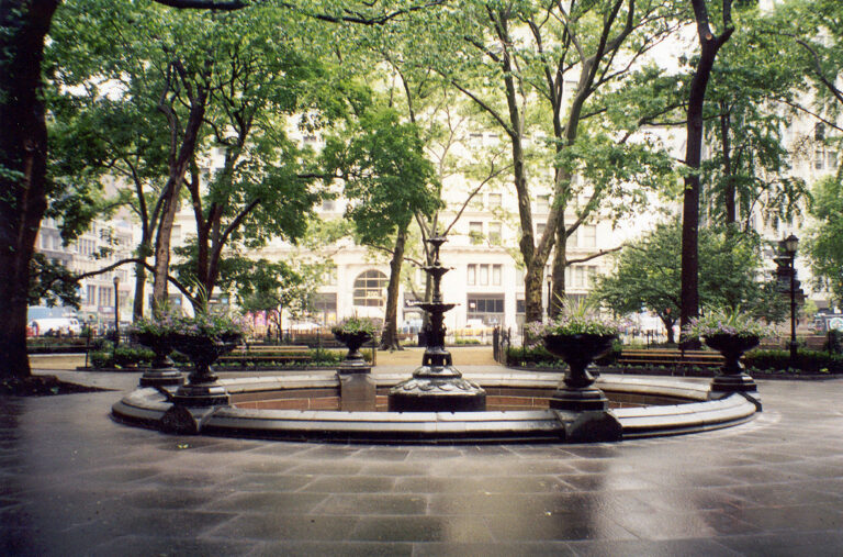 Photograph of the fountain at the park; the fountain is off and drained.