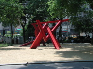 Photograph of art installation (intertwining red, metal bars).