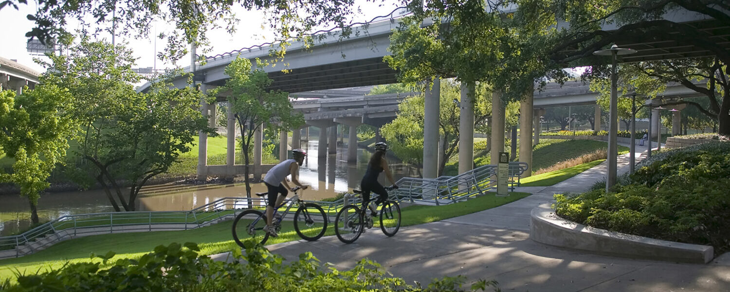 Two bicyclers biking on a park path that goes under roadway bridges. The bayou can be seen in the background.