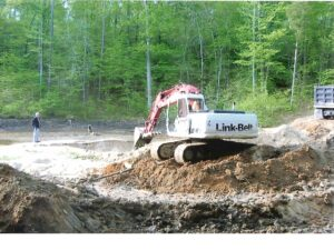 A backhoe removing silt deposited by a storm.