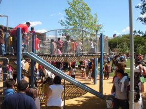A photograph of a play feature at Discovery Green with a large crowd of children and parents.