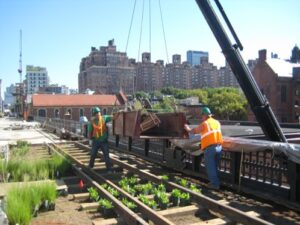 Two construction workers guiding materials being lifted from a crane onto the High Line.
