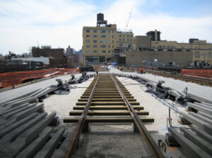A photograph of ongoing construction of the High Line, showing some of the concrete paving slabs in place and the railway in through the middle.