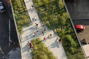 """A direct overhead image of the High Line above a """"Y""""-shaped path with several people strolling and a few sitting on benches."""