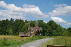 A photograph of an observation tower sited in one of the park's open meadows. The tower is made of wood and metal and is about one story high.