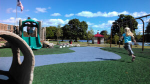Photograph of a girl running at the woodland-themed playground. Swings can be seen on the right, and a climbing structure and slide made to look like logs can be seen on the left. The surface is a mix of artificial turf and poured-in-place safety surfacing.