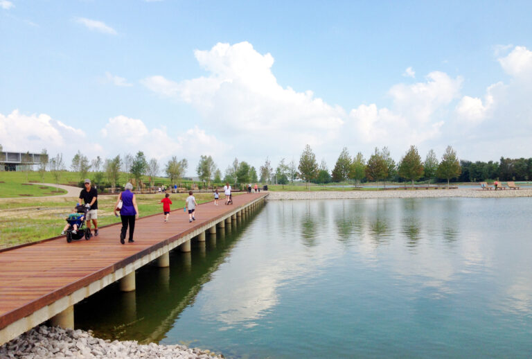 Image of a boardwalk at Shelby Farms at the edge of the lake. Visitors are seen walking and running across the boardwalk. Trees and the playground can be seen in the background.