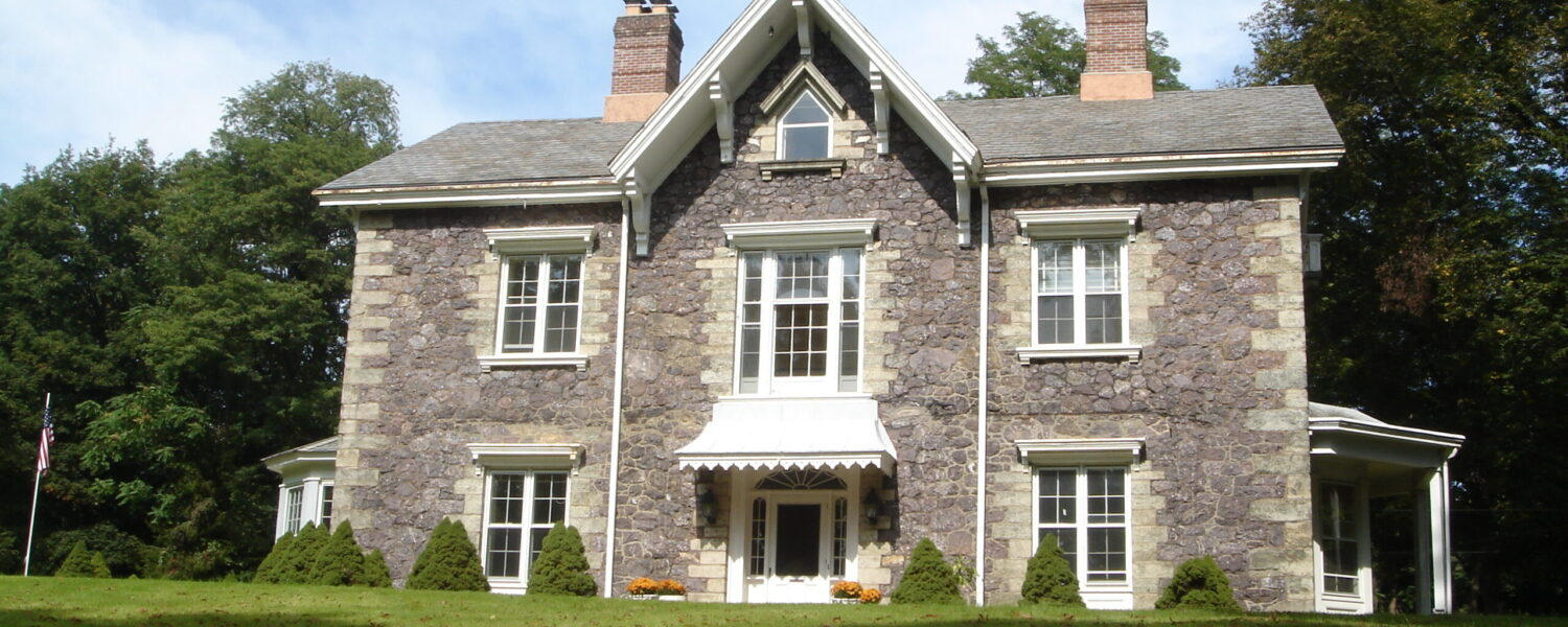 A photograph of the front of Willow Hall, a two-story house with attic, stone facade, and two chimneys.