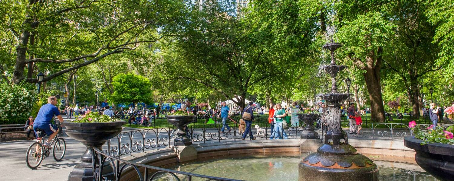 A photograph of Madison Square Park. Part of the fountain can be seen in the foreground, with people strolling along paths and sitting on benches in the background.