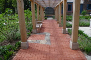 The stone outline of the historic privy is seen within the brick paving under the pergola.