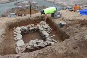 An archeaologist is excavating a historical privy. The privy is made of several layers of stone stacked to form the outline of a square.