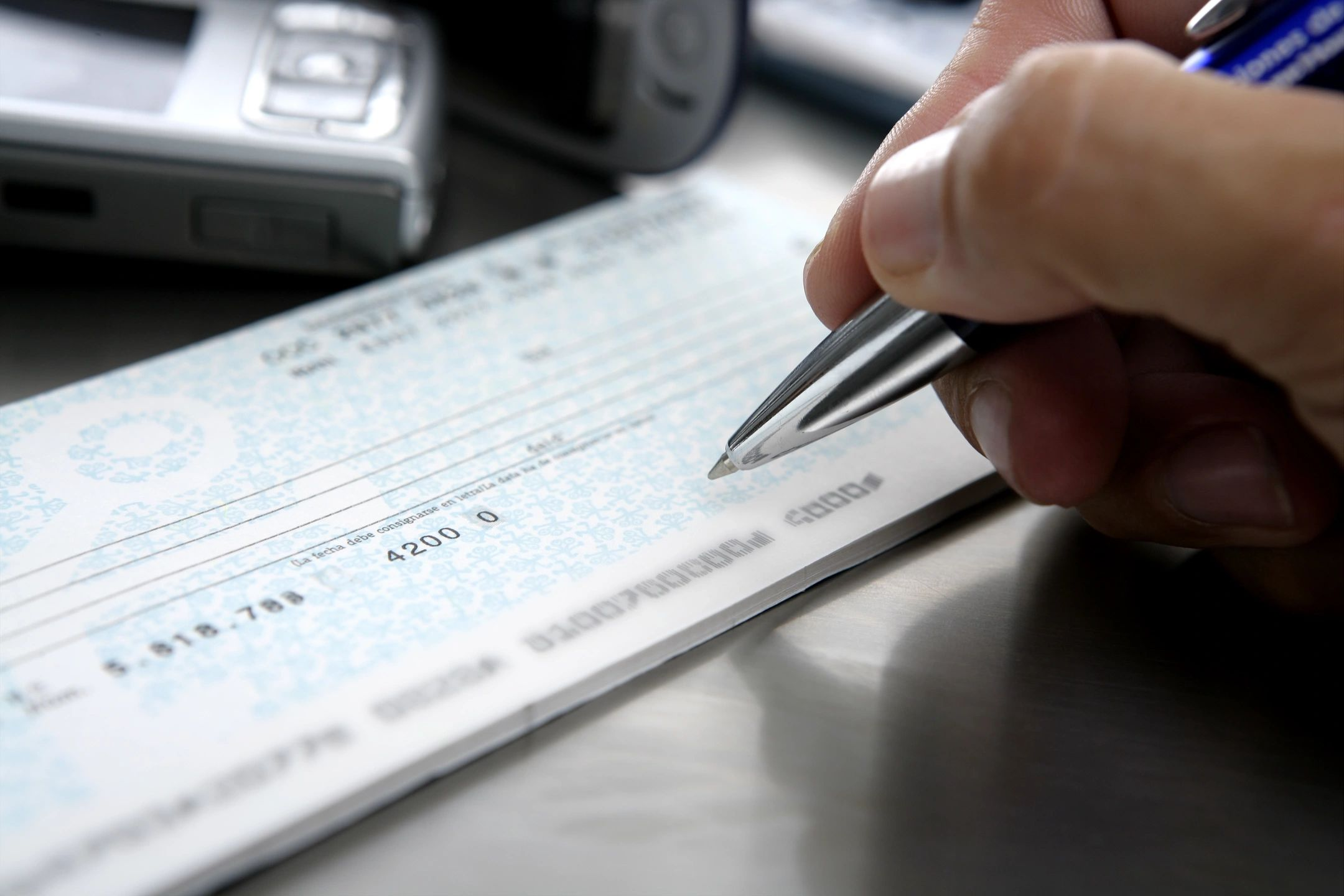 Chequing Accounts. image of cheque book and pen