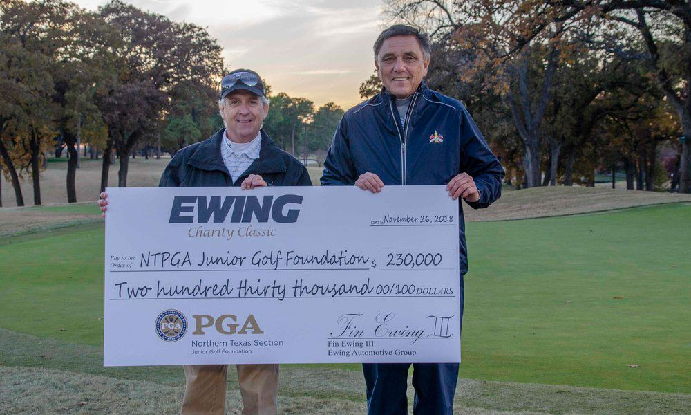 Fin Ewing III (left), owner of The Ewing Automotive Group, presents a check to Northern Texas PGA president Ronny Glanton with proceeds from the Ewing Charity Classic at Brook Hollow Golf Club in Dallas on Nov. 26, 2018.