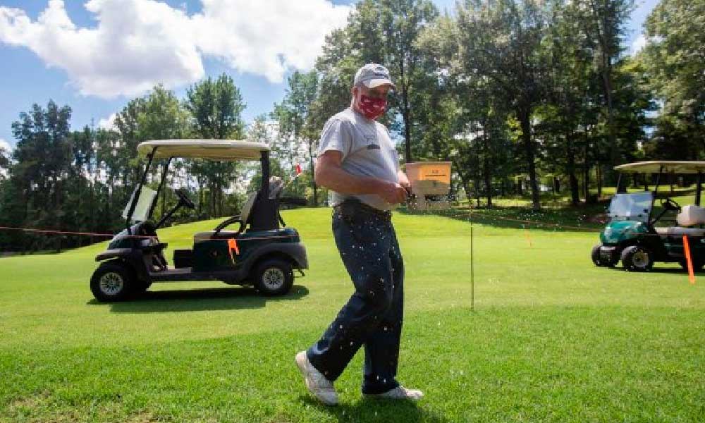 """Photos by Cheyenne Boone/The Herald Buffalo Trace Golf Course Superintendent Philip Volz spreads Bermuda grass seeds at the course in Jasper on Tuesday. He has worked at the course for 39 years and will retire in August. """"Out of the 39 years I've worked here, I've only been hit with a golf ball once,"""" Volz said."""