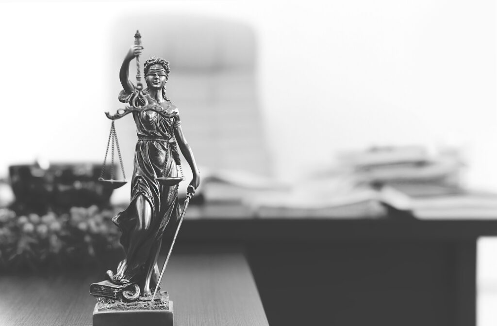 Picture of small statue of Lady Justice with desk in the background.