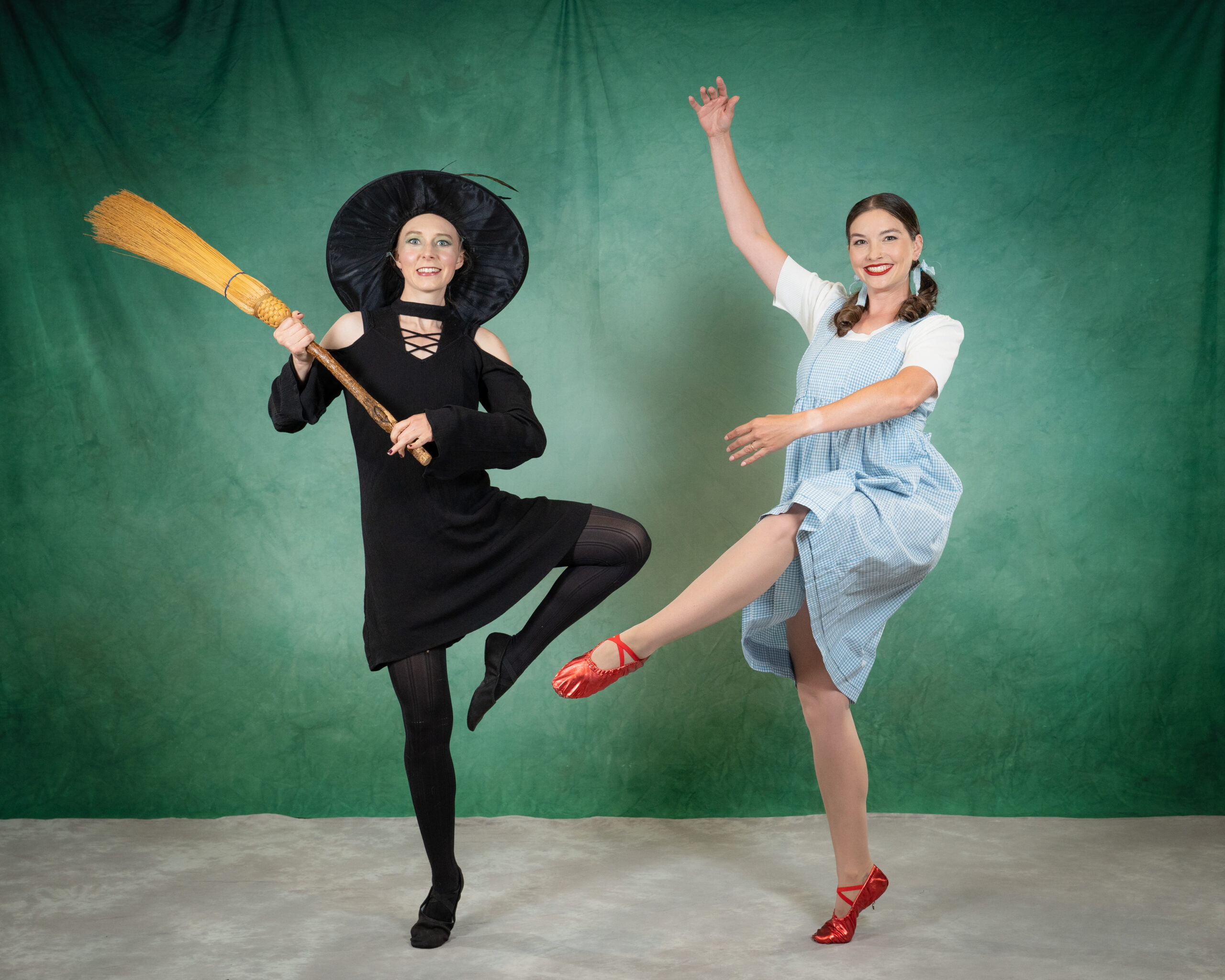 adult dancers in dorothy and wicked witch costumes