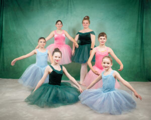 ballet dancers in blue, pink and green costumes
