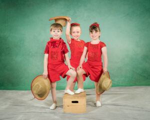 3 tumbling dancers in red costumes
