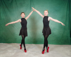 Pointe dancers in black costumes and red shoes