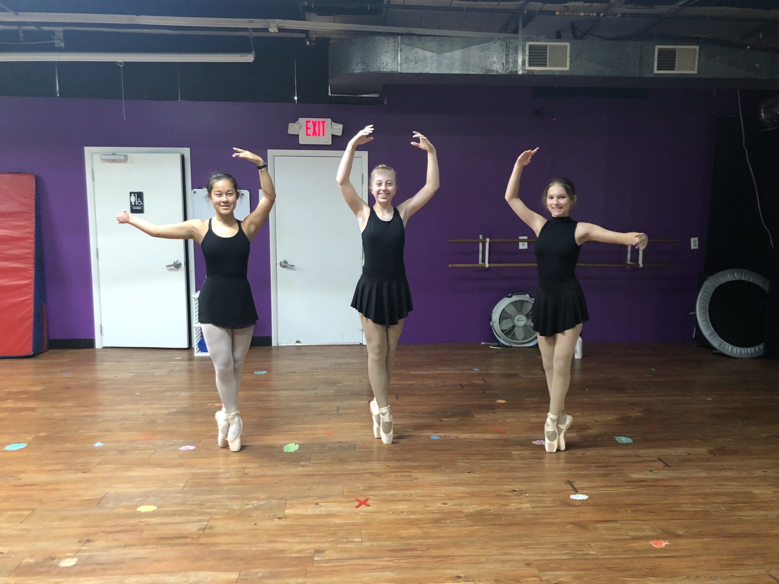 3 dancers standing on pointe in dress code