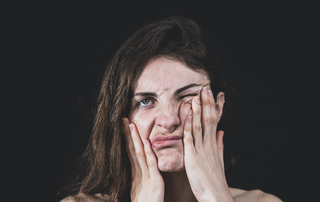 Woman with hands on face looking stressed out.