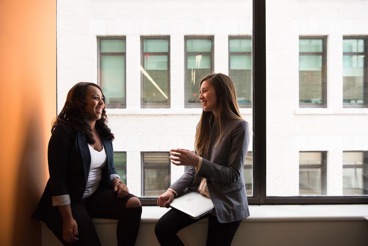 Two women talking and listening in an office window