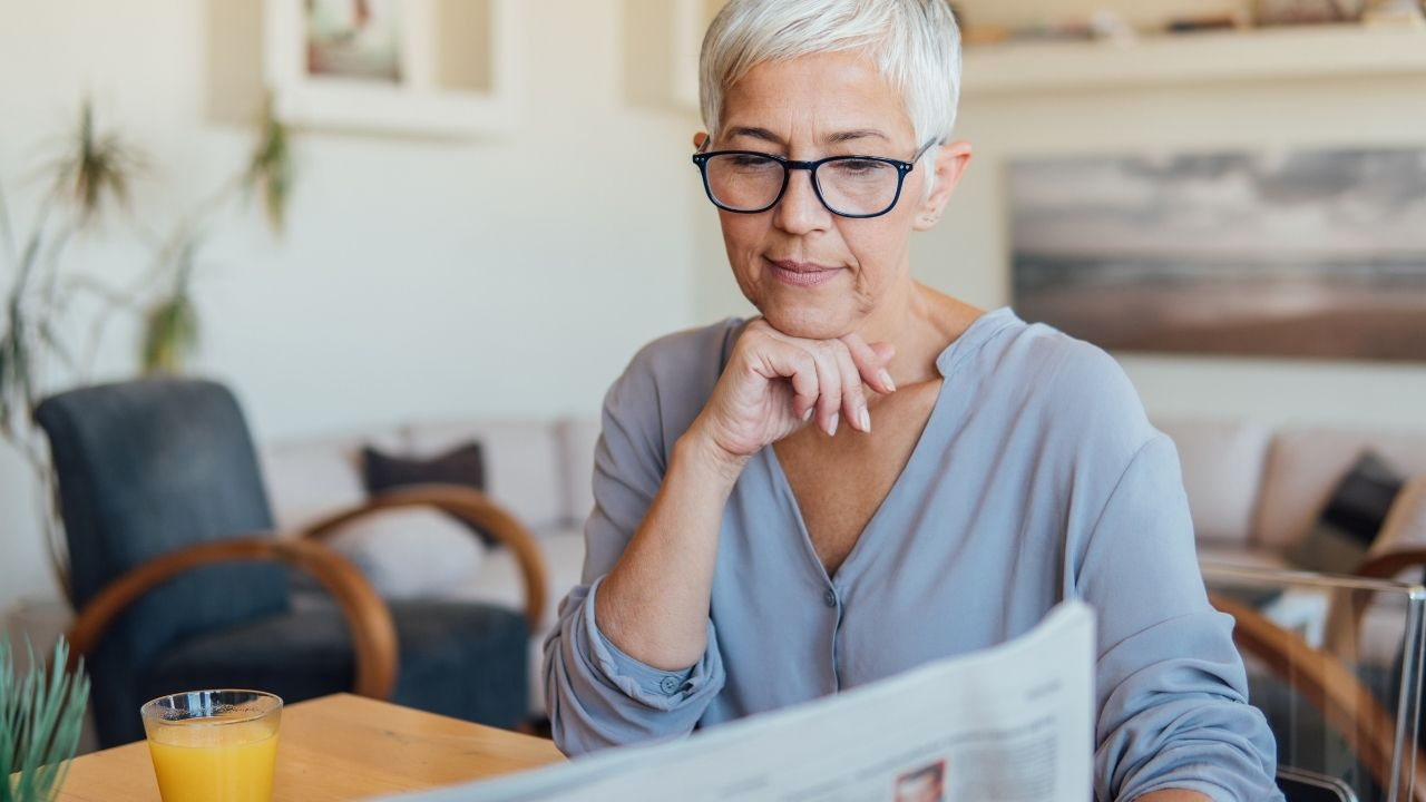 Photo of white haired woman reading paper to illustrate age discrimination.