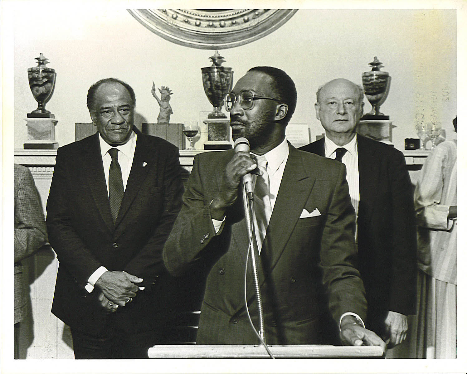 EARLY 1980'S:  Lloyd Williams (center) speaks as then NYPDCommissioner Benjamin Ward (left) and then Mayor Ed Koch listen intently.