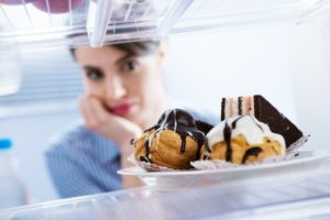 25919357-young-hungry-woman-in-front-of-refrigerator-craving-chocolate-pastries