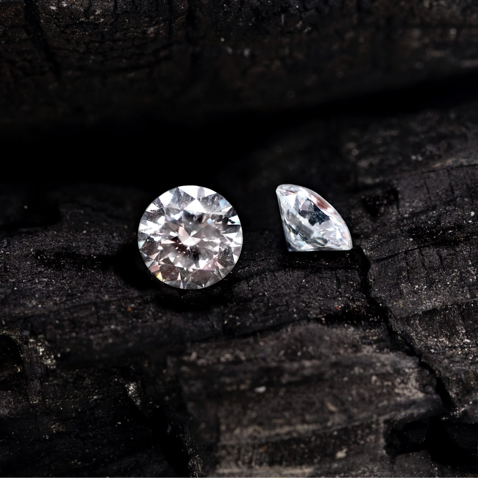 A picture of two round diamonds on black coal
