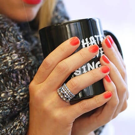 Stackable bands layered on a finger hold a coffee mug
